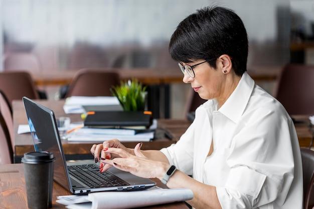 Коротко стриженная деловая женщина, работающая сбоку