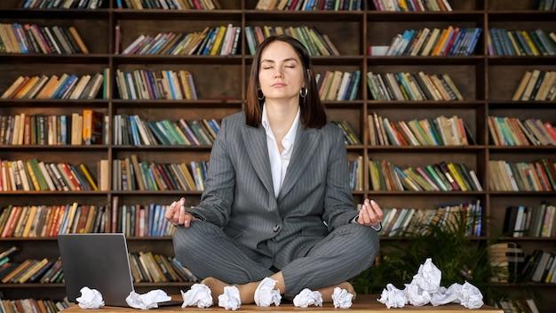 짧은 머리 여성 사업가는 구겨진 종이 시트와 책꽂이에 대고 노트북 사이에 나무 테이블에 요가 포즈에 앉아 명상