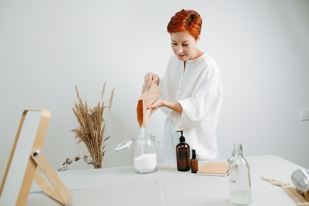 Химик с короткими волосами готовит смесь для экологически чистой косметики на столе. засыпание белого порошка в банку.