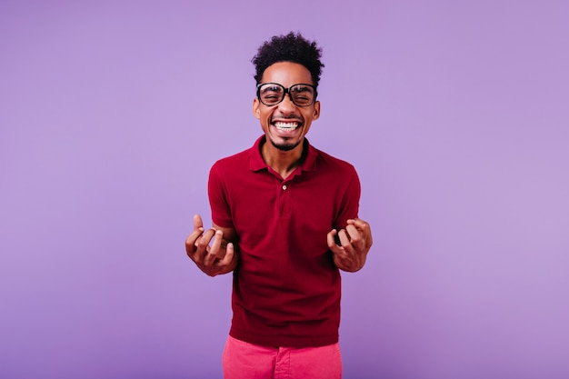 Modello maschio riccio dai capelli corti che ride. ragazzo africano ispirato in occhiali in posa.