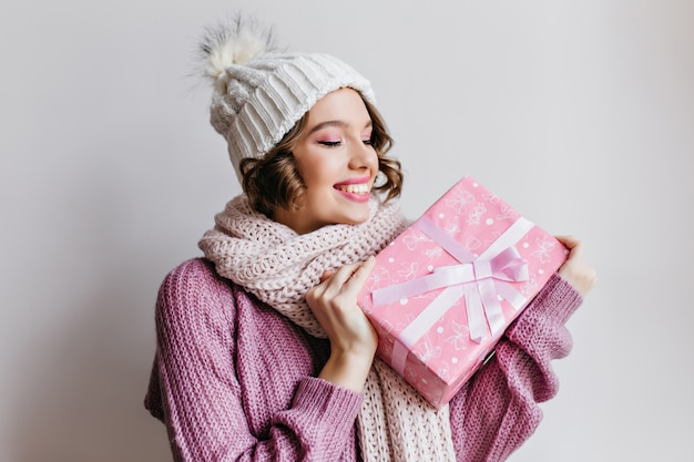 Short-haired european girl in hat posing emotionally, looking at new year present. indoor photo of amazed young lady in cute scarf holding pink gift.