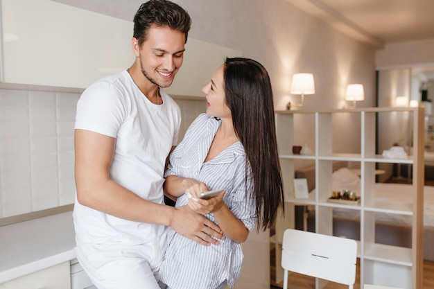 Short-haired european guy gently touching charming wife in blue pajama