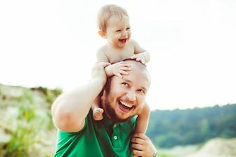 """""""肩で幼児を運ぶ短い髪の父"""""""