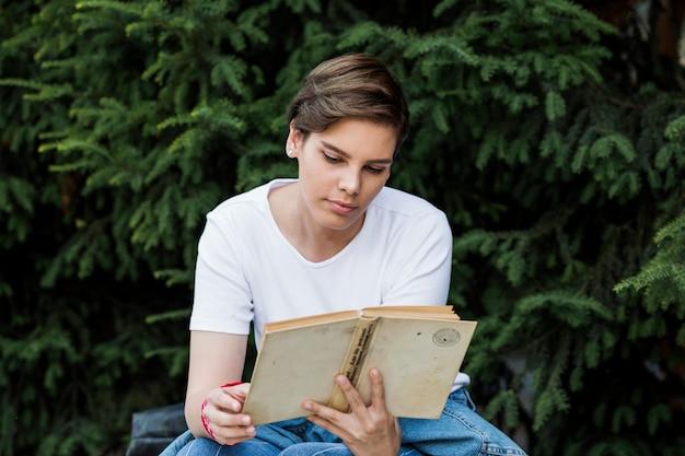Короткошерстная женщина, читающая книгу под деревом Бесплатные Фотографии