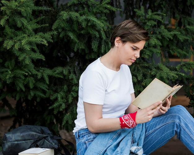 Короткошерстная женщина сидит с книгой в парке