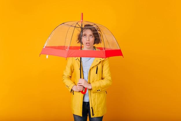 Девушка с короткой стрижкой выражает грустные эмоции во время фотосессии с зонтиком. женская модель с зонтиком готовится к дождливой погоде.