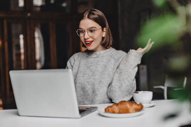 Short-haired girl with bright lipstick looks into laptop in surprise. portrait of woman in gray sweatshirt and stylish glasses in cafe.