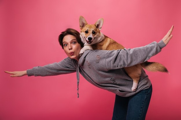 Short haired lady in hoodie holds and plays with dog. cool woman in grey sweatshirt and jeans poses with corgi on pink isolated background