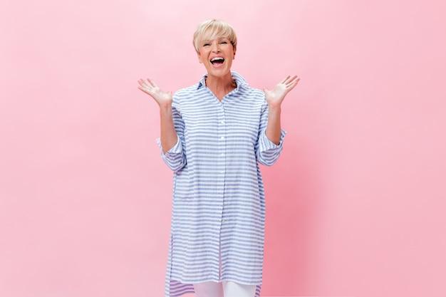 ピンクの背景に喜んでポーズをとる格子縞のシャツの短い髪の女性