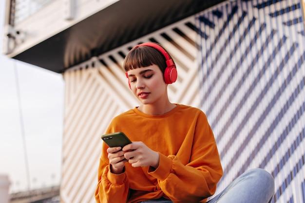 빨간 헤드폰을 쓴 단발머리 여성이 밖에서 전화를 들고 있다