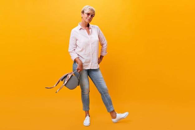 Signora dai capelli corti in jeans e camicia pone con la borsa su sfondo arancione