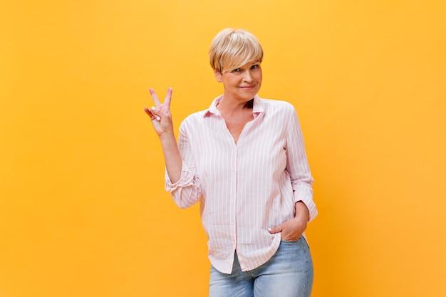 Signora dai capelli corti in camicia rosa che mostra il segno di pace su sfondo arancione