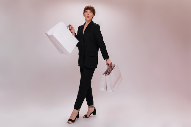 Short haired lady whistles and holds shopping bags. pretty woman in black suit moves with white packages on isolated backdrop