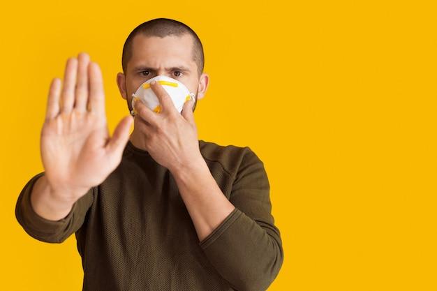 Короткошерстный мужчина с медицинской маской на лице показывает знак остановки ладонью, позирует на желтой стене со свободным пространством