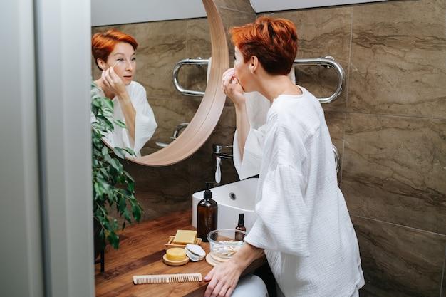 綿棒でアイメイクを修正する短髪の成熟した女性。彼女はバスルームの鏡の前に立っています。