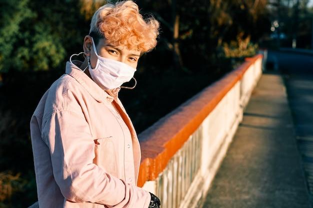 짧은 머리 분홍색 여자는 야외 공간에서 얼굴 마스크를 쓰고 있습니다.