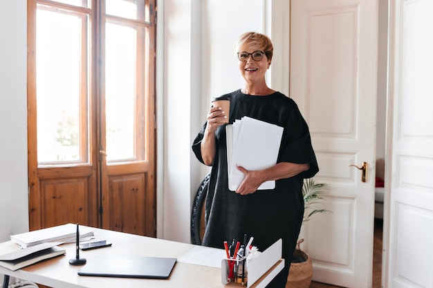 Short haired woman in black outfit holding coffee cup and paper sheets