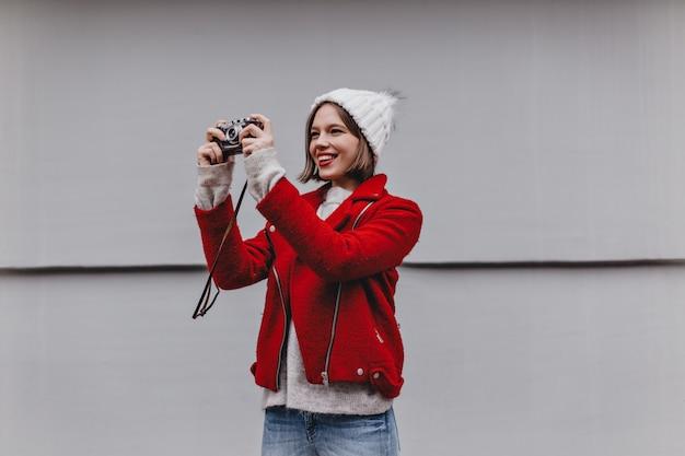 ニット帽と赤いコートを着た短い髪の女性がレトロなカメラで写真を撮ります。