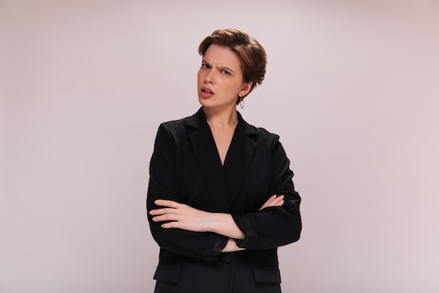 スーツを着た短髪の女性が誤解してカメラを覗き込む。黒のジャケットの女性は、孤立した背景に機嫌が悪いポーズをとる
