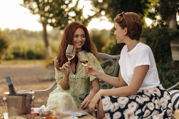 Short haired woman in light t-shirt and floral skirt smiling and sitting with ginger girl in yellow dress and holding glass with drink outdoor