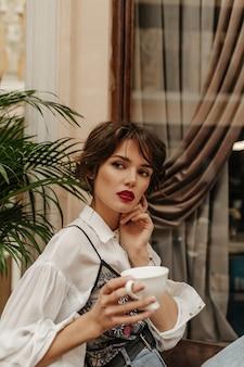 Donna dai capelli corti in camicia a maniche lunghe con labbra rosse che tiene tazza di caffè nel ristorante. donna con l'acconciatura castana pone nella caffetteria.