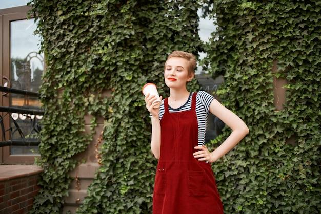 短い髪の女性の屋外で一杯の飲み物のライフスタイルの低木