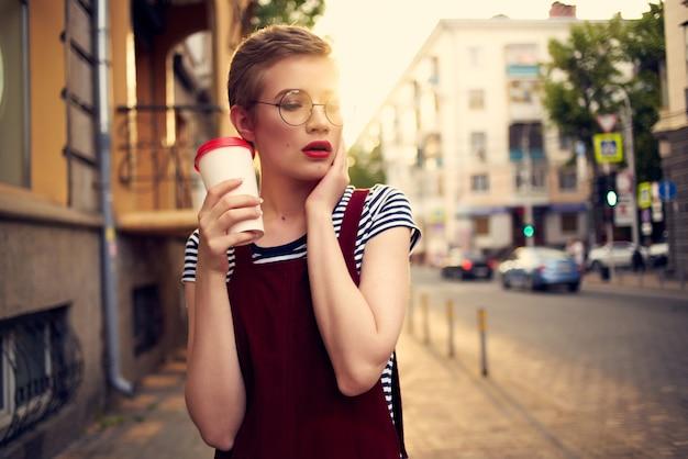 短い髪の女性の屋外カップドリンクウォーク夏