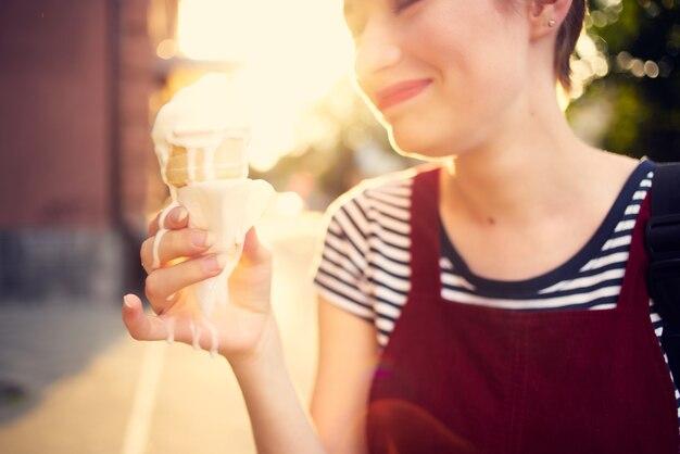 アイスクリームウォークライフスタイルを屋外で食べる短い髪の女性