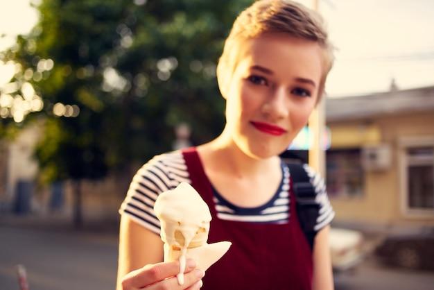 アイスクリームウォークを屋外で食べる短い髪の女性