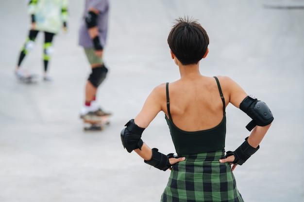 스케이트파크에서 다른 사람들을 바라보는 짧은 머리의 여자 스케이터. 그녀의 뒤에서.