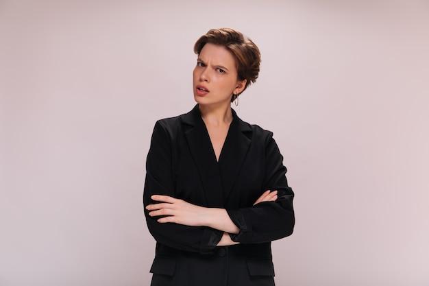 La donna dai capelli corti in vestito esamina la macchina fotografica con incomprensione. lady in black jacket pone di cattivo umore su sfondo isolato
