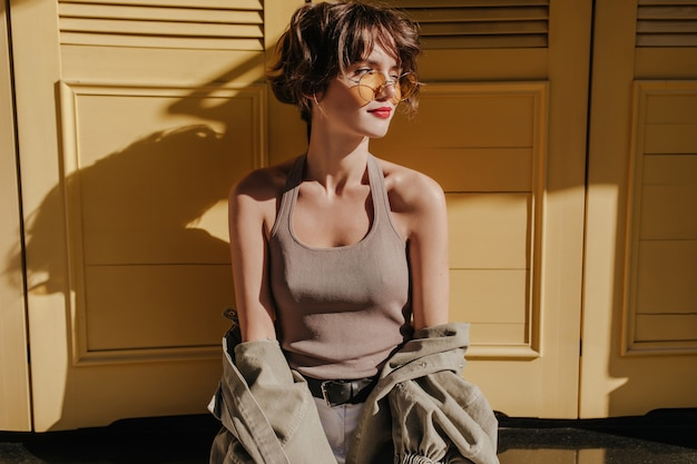 Short-haired woman in sunglasses posing on yellow doors. curly woman in undershirt with jacket looks away on yellow doors