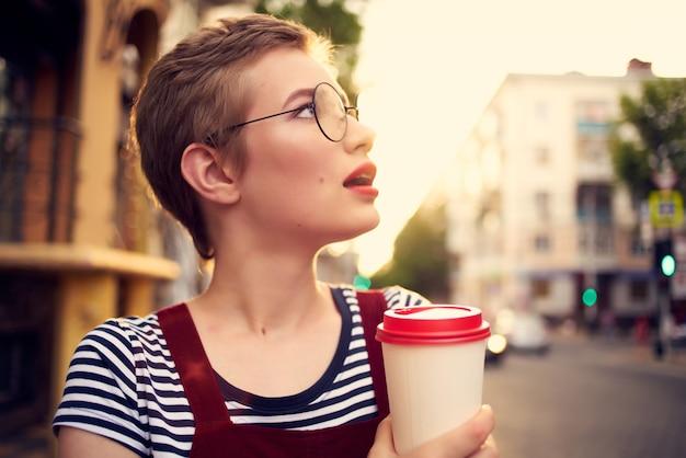屋外で眼鏡をかけている短い髪の女性は、レジャードリンクカップを歩きます