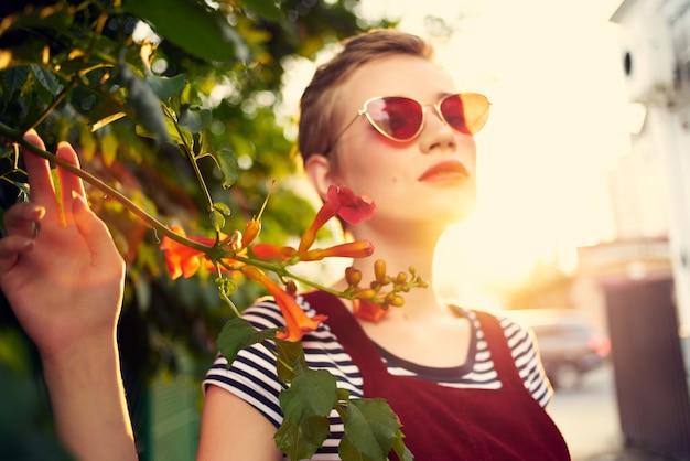 야외 꽃 장식 선글라스를 착용 하는 짧은 머리 여자. 고품질 사진