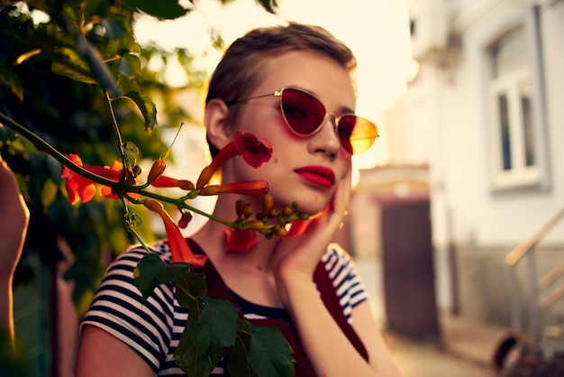야외 꽃 장식 선글라스를 착용하는 짧은 머리 여자