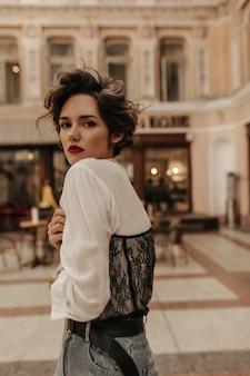 Donna dai capelli corti in camicetta bianca con maniche lunghe e pizzo scuro posa in città. donna con capelli ricci e labbra rosse in strada.