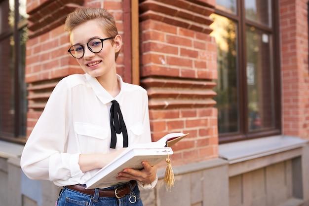 야외에서 독서 교육을 손에 들고 있는 짧은 머리 여자