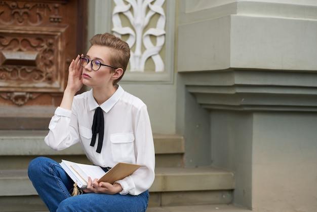 本のコミュニケーションで街を歩いている眼鏡をかけた短い髪の女性。高品質の写真