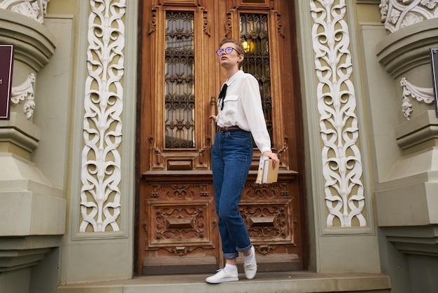 本のコミュニケーションで街を歩いている眼鏡をかけた短い髪の女性