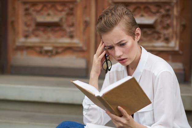 本のライフスタイルで街を歩く眼鏡をかけた短い髪の女性