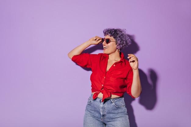 La donna dai capelli corti con l'acconciatura corta viola in abito elegante sorride e tiene gli occhiali da sole sul lilla isolato.