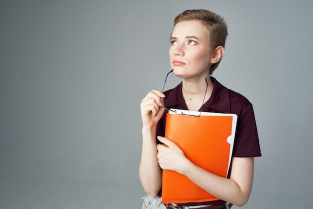 赤いフォルダートレーニング教育スタジオを持つ短い髪の女性