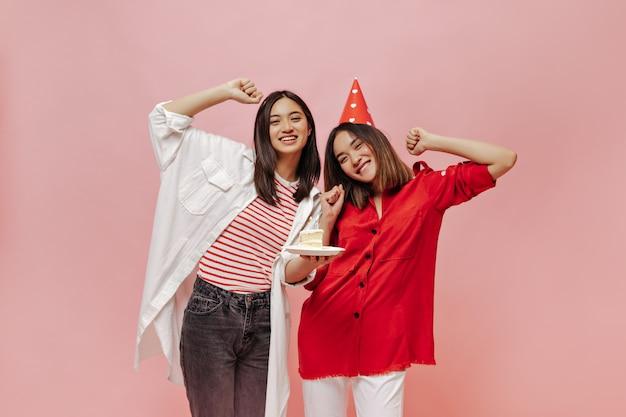 짧은 머리 여성들은 분홍색 외진 벽에서 생일을 축하합니다. 줄무늬 티셔츠와 특대형 셔츠를 입은 매력적인 소녀가 b-day 케이크를 들고 있다