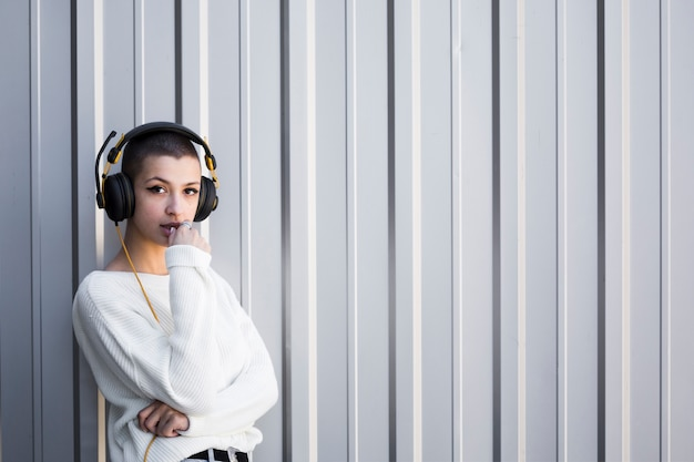 Short haired young woman listening to music and looking at camera