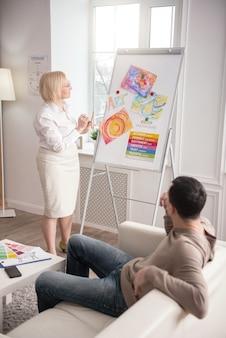 簡単な紹介。ホワイトボードを見ながらアートセラピーについて話し合う2人の気配りのある同僚の心理学者