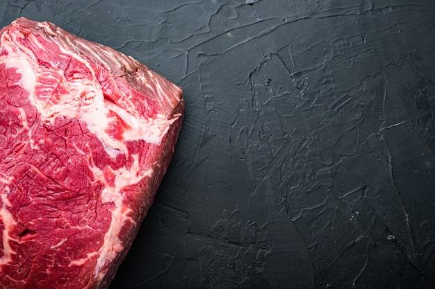 Short loin raw beef steak cut, on black table, top view,