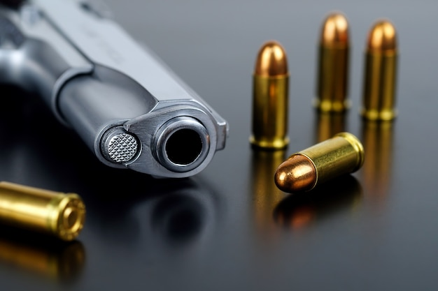 Short pistol and ammunition put on a black background