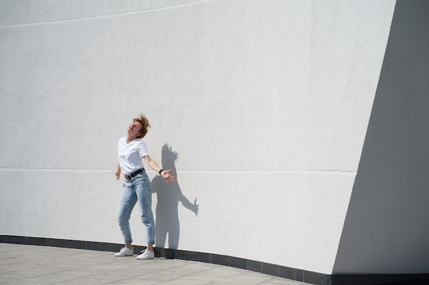 Short redhair woman dancing in front of white wall outdors