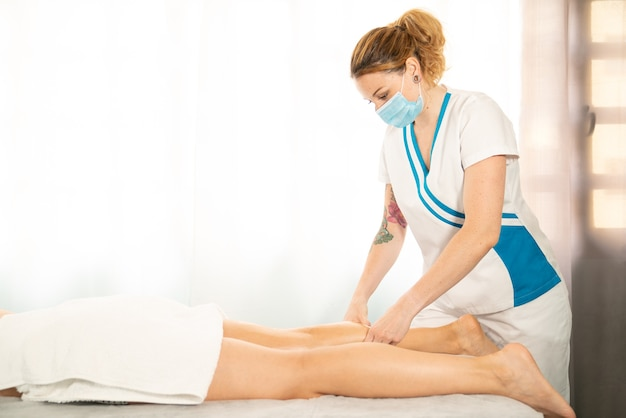 Short shot of an ethnic caucasian professional woman giving a physiotherapeutic massage on the leg of a client lying on a stretcher wearing a face mask due to the covid 19 coronavirus pandemic