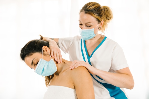 Короткий снимок профессиональной женщины кавказской национальности, которая делает физиотерапевтический массаж шеи в маске из-за пандемии коронавируса covid 19